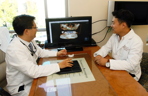 Dr. Kim and Dr. Bae looking at screen